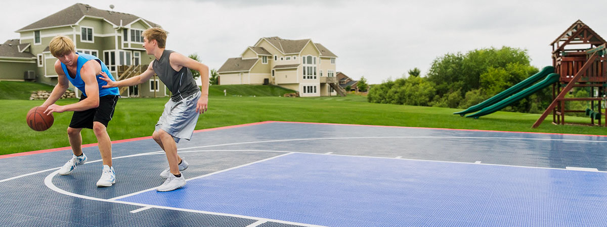 Two teens playing basketball on one of our outdoor basketball court
