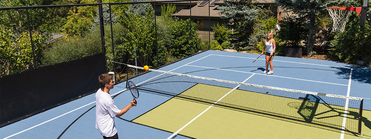Two youth are playing tennis on their backyard multi-court