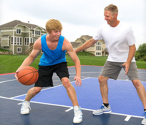 A father and his son are playing basketball on an SnapSport outdoor BounceBack court.